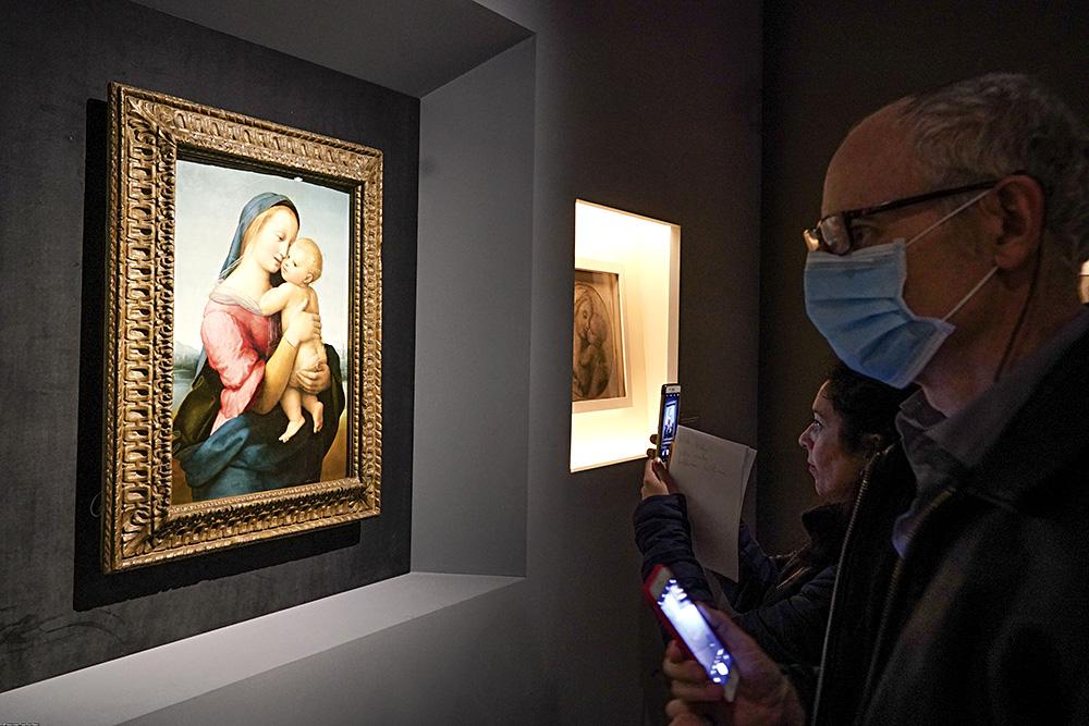 """Н фотографии изображены посетители выставки """"Рафаэль"""" в римской галерее. На них надеты маски, в мерах предосторожности. Причиной является коронавирус."""